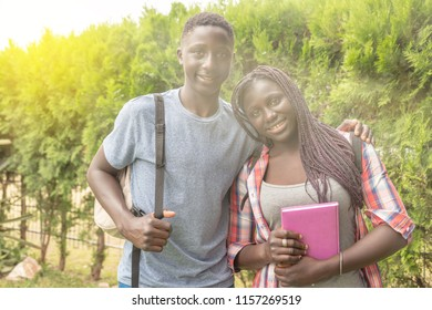 African teenager couple happy smiling outdoor with books, sun rays coming from the sky.