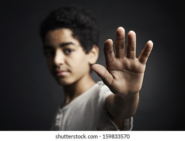 African teenager holds hand out as stop sign