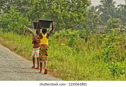 African teenagers carry a luggage on their heads. Young African girls walk along the road. Countryside. Lifestyle in developing countries of Africa. Ghana.