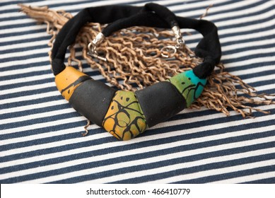 African tribal bib necklace on striped fabric. Handmade jewelry of polymer clay. Background with jewelry. African style.