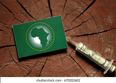 African Union flag on a stump with syringe injecting money in flag