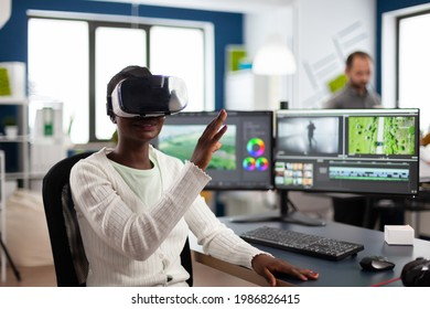African video editor experiencing VR goggles, gesturing, editing video film montage working with footage and sound on computer with two displays. Videographer processing movie in creative agency