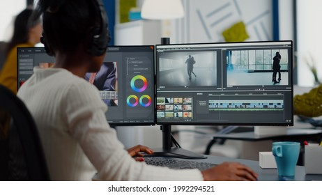 African video editor working with footage and sound, editing new project cutting film montage sitting in modern agency office. Woman using computer processing movie in post production software