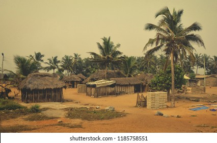 African village. Houses, barracks with thatched roof with palm trees in background. Rural lifestyle of West Africa. Traditional way of life in developing countries. Ghana, village near Atoko.