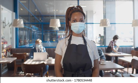 African waitress wearing protective mask and gloves standing in cafe during covid-19 preventing. Afro-american barista putting on safety mask working in cafe after reopening during pandemic