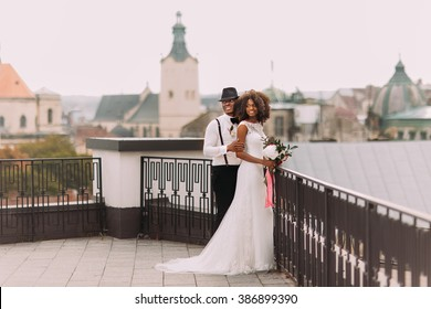 African wedding couple on the rooftop. Amazing european Lviv architecture on background