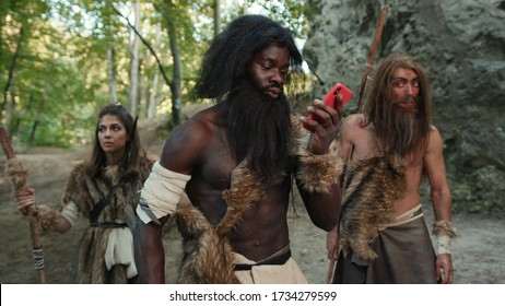 African wild tribe of cavemen walking in the woods. In focus black caveman talking on phone using miracle technology in prehistoric stone-age period. Fun and evolution.