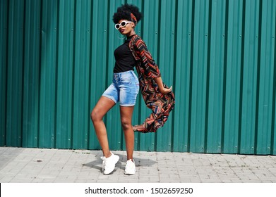 African woman with afro hair, in jeans shorts and white sunglasses posed against green steel wall.