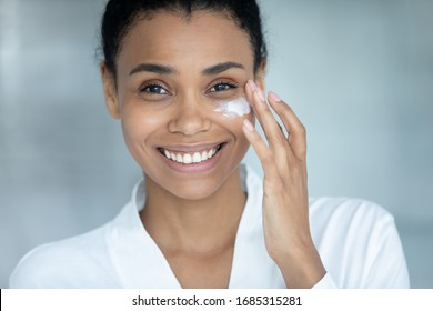 African woman apply day creme close up female attractive happy face. Using facial cream after 30s to keep skin collagen and elastin rate, hydrate and nourish it. Beauty treatment and skincare concept