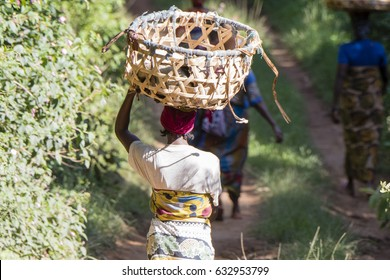 African Woman with Basket on Head Walking on a Rural Road in Tanzania