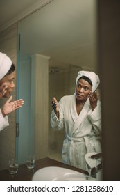 African woman in bathrobe applying cosmetic lotion to take care of the skin in the bathroom. face care concept. Reflection of mature woman in the mirror applying facial cosmetic in bathroom.