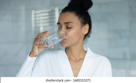 African woman in bathrobe holding glass drink filtered still clear water, preventing of skin dehydration, caring about drinking regimen aqua balance in body, taking pill or daily supplements concept