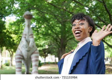 african woman being surprised at dinosaur