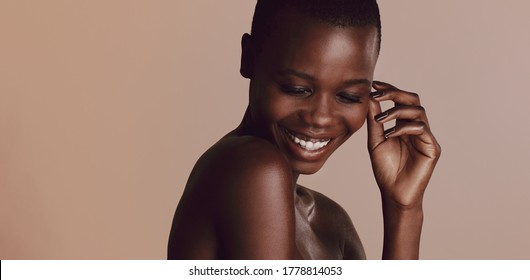 African woman with buzz cut hairstyle looking down and smiling. Female fashion model smiling against beige background.
