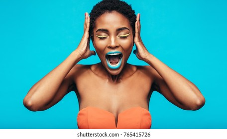 African woman with colorful makeup screaming against blue background. Female fashion model with mouth open and hands on ears.
