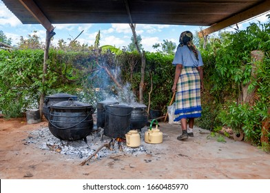 African woman, cooking in few Big pots outdoors in the village, African kitchen in the backyard