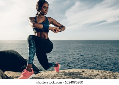 African woman doing stretching exercises by the beach. Female doing warm up stretches on rocks at the beach.