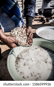 An African Woman Draining Starch Water From Soaked Samp And Kidney Beans During Meal Preparation At A Wedding In Botswana, Africa.