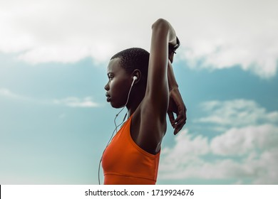 African woman with earphones doing hand stretching exercise outdoors. Female in sportswear doing warmup workout outdoors against sky.