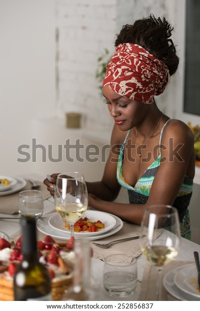African woman eating at home and drinking wine and looking very happy