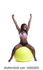 african woman exercising with a yellow pilate ball