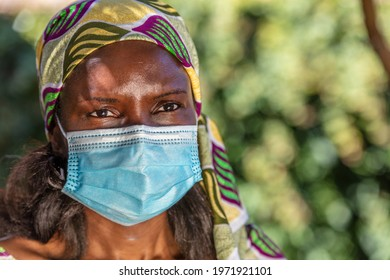 African woman, female in Africa, wearing traditional clothes and face mask in Coronavirus COVID-19 pandemic