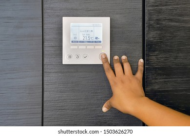 African woman hand try to turn on the new air condition in room, in the hotel room. African female hands on the air conditioning control panel. Hand girl setting temperature air condition.