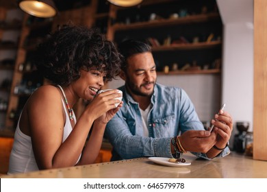 African woman having coffee with her boyfriend showing something on mobile phone. Young couple at coffee shop looking at smart phone.