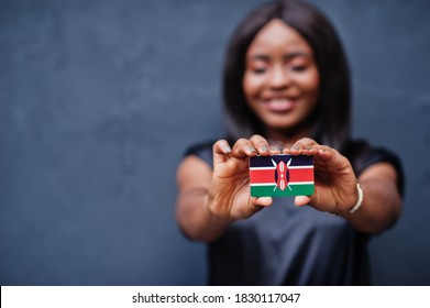 African woman hold small Kenya flag in hands.