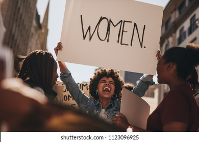 African woman holding a banner and laughing during women march. Group of female demonstrating outdoors with placards.