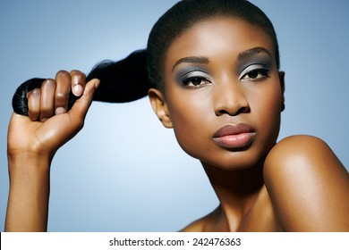 African woman holding her pony-tail in hand. Can be used for haircare or other beauty concepts.