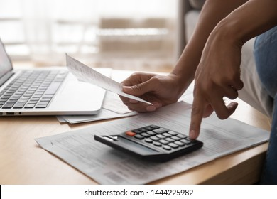 African woman holding paper bills using calculator, close up vie