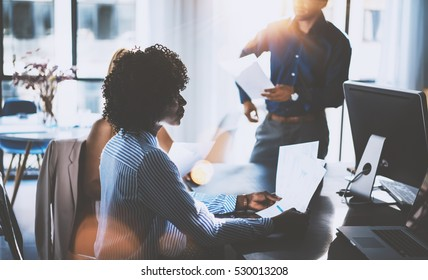 African woman holding papers hands and talking with partners.Young team of coworkers making great business discussion in modern coworking office.Teamwork concept.Horizontal, blurred background,flares