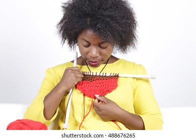 African woman knitting, sitting on a white couch. Mixing brown with red colour.