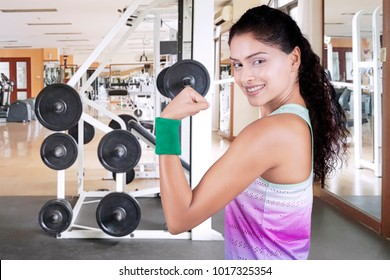 African woman looking at the camera while showing her arm muscle in the fitness center