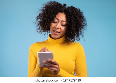 African woman making notes in planner, mature lady holding pen. She writes future plans and to-do list in notebook for week or month. Keeping personal diary on blue studio background.