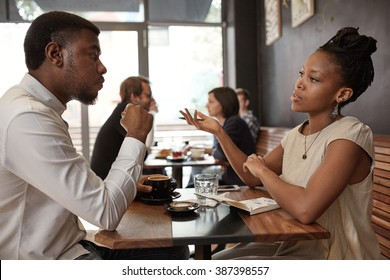 African woman and man discussing business ideas at busy cafe