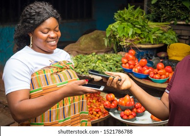 african woman in a market receiving payment via contactless transfer of funds from a customer using their mobile phones
