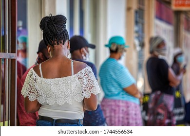 African woman with a mask standing in the cue at the shops