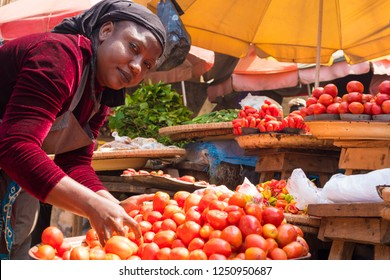african woman picking tomatoes in a tray in a local african market