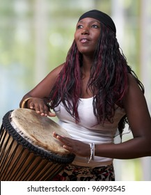 An African woman plays the djembe drum
