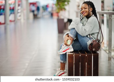 African woman posed in sweater and jeans posed at mall, sitting on bench with her mobile phone.