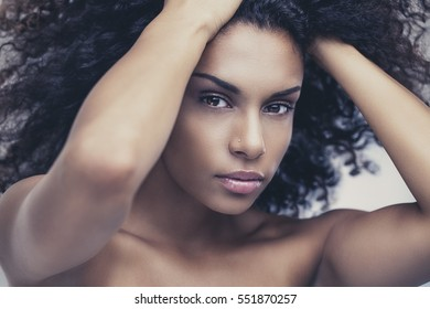 African woman posing with hands in hair.