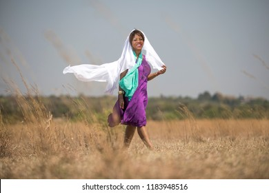 African woman with purple dress and white and turquoise scarf walking in a field on a windy day.