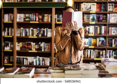 African woman reading a book at a bookstore.