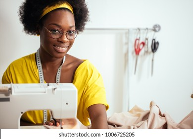 african woman seamstress sitting and sews on sewing machine. Hobby sewing as small business concept