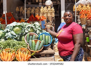 African woman selling organic fruits and Vegetables in the farmers market