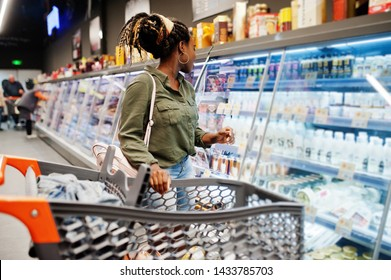 African woman with shopping cart choose yogurt bottle from fridge at supermarket.