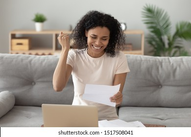 African woman sitting on couch at home holding paper reading letter from bank feels happy about loan approval, overjoyed american female makes yes gesture with hand celebrate getting new job concept
