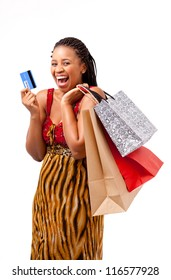 African woman smiling holding shopping bags and a blank card on an isolated background